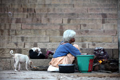 Varanasi. MP117: A poor old homeless woman cooks food on the ghats at Varanasi, Uttar Pradesh, India Stock Image
