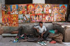 Varanasi. MP106: A roadside cobbler at Varanasi, Uttar Pradesh, India. Behind him are poster of Hindu gods and goddess Stock Photo