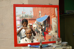 Varanasi. Reflection of a barber in a mirror shaving the head of a man on the ghat at Varanasi, Uttar Pradesh, India Stock Image