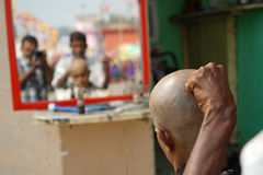 Varanasi. Reflection of a barber in a mirror shaving the head of a man on the ghat at Varanasi, Uttar Pradesh, India Royalty Free Stock Image
