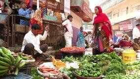 VARANASI, UTTAR PRADESH, INDIA, 10 BRENGT 2019 in de war - een mens door groenten en greens op zijn plaats bij Indische Bazaar wo stock footage