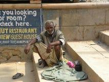 Varanasi, Uttar Pradesh, India - November 2, 2009 een oude mensenzitting dichtbij op de stappen dichtbij ghats Royalty-vrije Stock Afbeelding