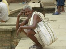 Varanasi, Uttar Pradesh, India - November 2, van 2009 Oude mensenzitting dichtbij ghats met witte zak en het glimlachen Stock Fotografie