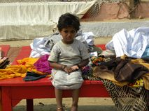 Varanasi, Uttar Pradesh, India - November 2, 2009 A young girl sitting on the bench in Varanasi ghats. A young female child sitting on the bench in the ghats Stock Images