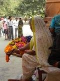 Varanasi Uttar Pradesh, Indien - November 2, 2009 en gammal kvinna i den vita sareen som säljer nya blommor Royaltyfri Bild