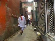 Varanasi Uttar Pradesh, Indien - November 3, 2009 Man att gå i bakgatorna Arkivbilder