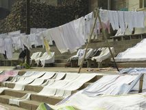 Varanasi, Uttar Pradesh, Indien - November 2, 2009 som är vita och färgrik kläder som ut hänger för att torka Royaltyfri Bild