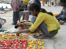 Varanasi, Uttar Pradesh, Indien - November 2, 2009 a-ung flickasammanträde på ghatsna och sälja poojaobjekt och blommor Arkivbild