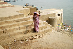 Varanasi. A woman sweeper cleans the ghat along the Ganges River or Ganga River in Varanasi, Uttar Pradesh, India Royalty Free Stock Photo