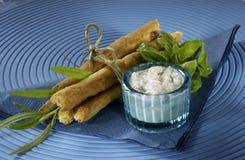 Varas com o queijo de feta, amarrado com corda, fundo azul, mergulho branco, ervas Imagem de Stock Royalty Free