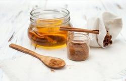 Varas de canela à terra, de mel e de canela no fundo branco Fotografia de Stock