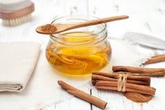 Varas de canela à terra, de mel e de canela no fundo branco Fotos de Stock