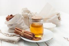 Varas de canela à terra, de mel e de canela no fundo branco Foto de Stock