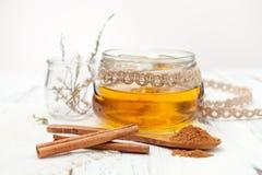 Varas de canela à terra, de mel e de canela no fundo branco Fotos de Stock Royalty Free