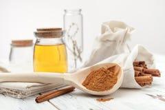 Varas de canela à terra, de mel e de canela no fundo branco Foto de Stock Royalty Free