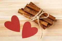 Varas de canela amarradas com guita e corações vermelhos em um fundo de madeira Foto de Stock Royalty Free