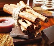 Varas de canela com as garrafas do chocolate e da essência Fotografia de Stock