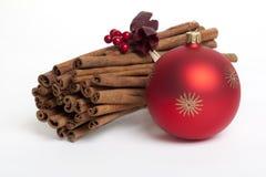 Varas de canela com a esfera vermelha da árvore de Natal Imagens de Stock