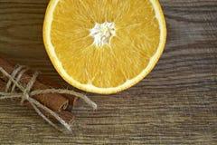 Varas de canela e laranja fresca cortada fotografia de stock royalty free