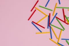 Varas de madeira coloridas contra o fundo cor-de-rosa imagens de stock royalty free