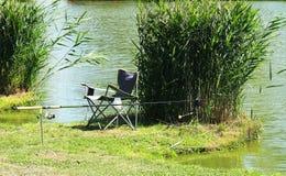 Varas de pesca, cadeira perto dos juncos na costa do l de pesca imagem de stock royalty free