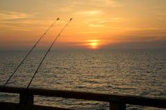 Varas de pesca em um fundo do por do sol no mar Báltico Fotografia de Stock