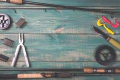 Varas de pesca, equipamentos de pesca, linhas, faca e alimentadores no fundo de madeira verde com espaço livre Fotos de Stock Royalty Free