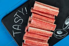 Varas de Surimi em Tray With Tasty Text Sign preto foto de stock