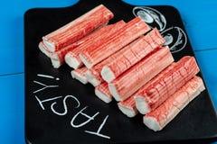 Varas de Surimi em Tray With Tasty Text Sign preto imagem de stock royalty free