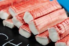 Varas de Surimi em Tray With Tasty Text Sign preto imagens de stock royalty free