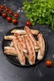 Varas do caranguejo na placa preta com salsa e tomates no fundo preto imagem de stock