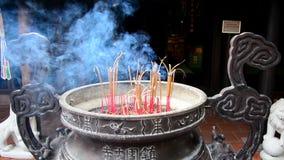 Varas do incenso que queimam-se no potenciômetro gigante na frente do templo budista vídeos de arquivo
