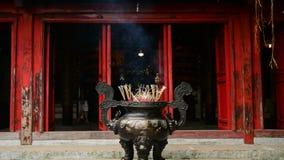 Varas do incenso que queimam-se no potenciômetro gigante na frente do templo budista filme