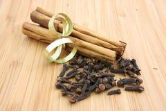 Varas e cravos-da-índia de canela em uma placa de madeira Fotografia de Stock Royalty Free