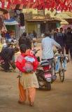 Vardagsliv i Bhaktapur, Nepal Kvinna med barnet, man med cykeln, studenter i likformig arkivbilder