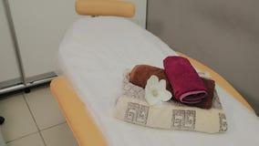 Vardagsrum f?r thai massage med handdukar, kuddar och blommor i tomt rum arkivfilmer