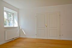 Vardagsrum i en gammal byggnad - lägenhet med den dubbla dörren och parkett efter renovering arkivfoto