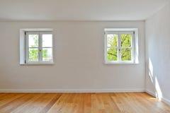 Vardagsrum i en gammal byggnad - lägenhet med träfönster och parkett efter renovering arkivfoton