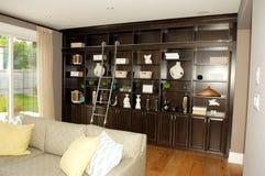 Vardagsrum i ett nytt hus med bokhyllor royaltyfria foton