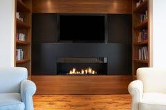 Vardagsrum i modernt hem med TV och spisen arkivfoto