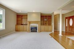 Vardagsrum i plan för öppet golv med foajésikt och träingångsdörren arkivbilder