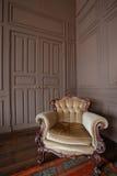 Vardagsrum med den antika stilfulla beigea fåtöljen Royaltyfri Foto