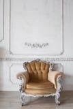 Vardagsrum med den antika stilfulla beigea fåtöljen på lyxiga vita beståndsdelar för roccoco för stöpningar för stuckatur för väg Arkivfoton