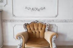 Vardagsrum med den antika stilfulla beigea fåtöljen på lyxiga vita beståndsdelar för roccoco för stöpningar för stuckatur för väg Royaltyfri Bild