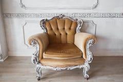 Vardagsrum med den antika stilfulla beigea fåtöljen på lyxiga vita beståndsdelar för roccoco för stöpningar för stuckatur för väg Arkivbild