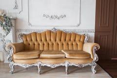 Vardagsrum med den antika stilfulla beigea soffan på lyxiga vita beståndsdelar för roccoco för stöpningar för stuckatur för väggd Arkivbilder