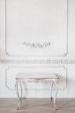 Vardagsrum med den antika stilfulla ljusa färgade tabellen på lyxig vit roccoco för stöpningar för stuckatur för väggdesignbasrel Royaltyfri Foto
