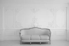 Vardagsrum med den antika stilfulla ljusa soffan på lyxiga vita beståndsdelar för roccoco för stöpningar för stuckatur för väggde Royaltyfri Bild
