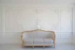 Vardagsrum med den antika stilfulla ljusa soffan på lyxiga vita beståndsdelar för roccoco för stöpningar för stuckatur för väggde Royaltyfri Foto