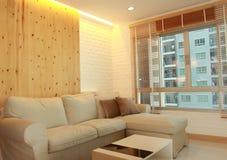 Vardagsrum med den ljusa wood panelen och gömd belysning Arkivfoto